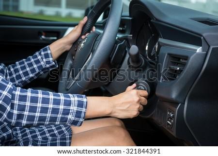 Women driver hand inserting car key and starting engine. - stock photo