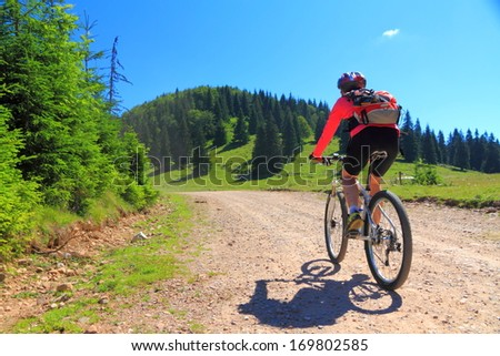 Women during mountain biking trip on difficult alpine road - stock photo