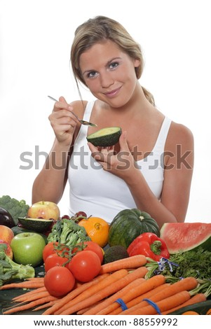 Women eats ripe Avocado at a table of an abundance of fruit and vegetables - stock photo