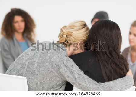Women embracing in rehab group at therapy session - stock photo