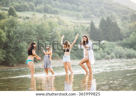 Women enjoy summer time on river beach - stock photo
