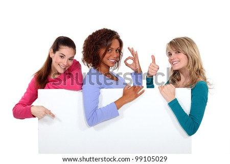 Women enthusiastically holding up a blank sign - stock photo
