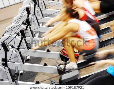 Women exercising in the gym on rowing machines - stock photo