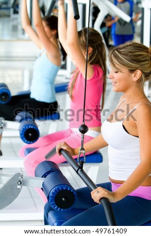 women exercising on machines at the gym - stock photo