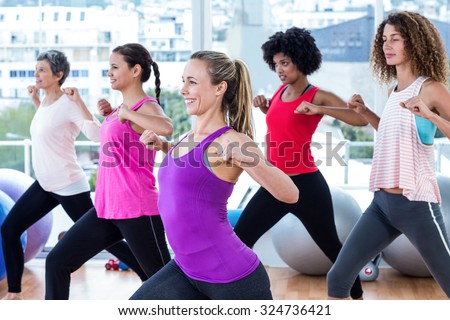 Women exercising with clasped hands and stretching in fitness studio - stock photo