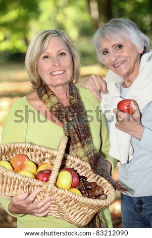 Women gathering chestnuts and apples - stock photo