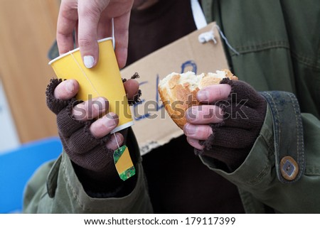 Women giving hot tea to poor homeless man - stock photo