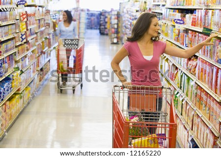 Women grocery shopping in supermarket - stock photo