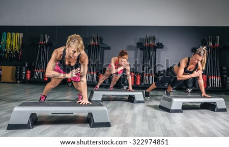 Women group training hard over steppers in aerobic class on a fitness center. Sport and health concept. - stock photo