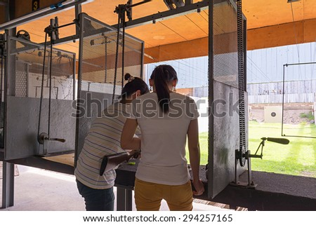 women guide for friend how to use the rifle shooting target.  - stock photo