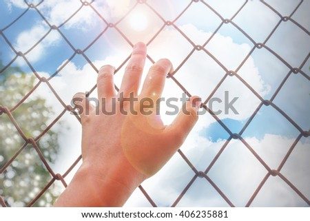 Women hand catching rusty iron bar with tree and wide blue sunny sky background and copy space, freedom desire concept