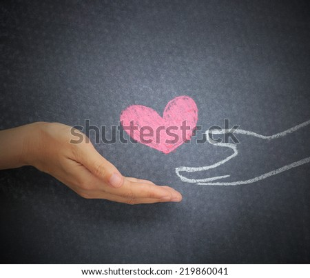 Women hand giving doodle heart to doodle hand on chalkboard background. - stock photo