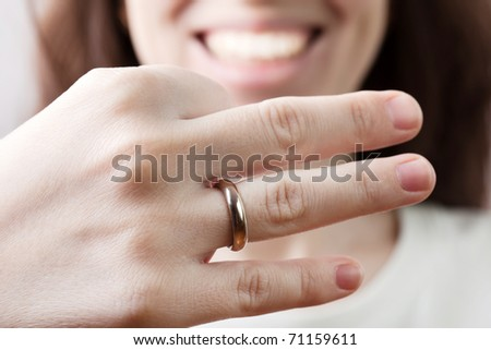 Women hand holding just married gold wedding ring - stock photo