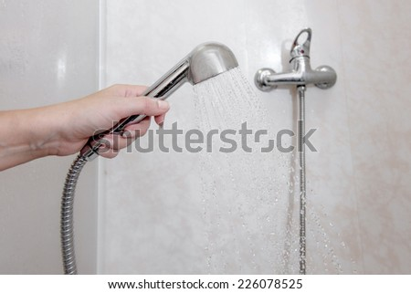 Women hand holding shower head with pouring water in domestic bathroom, a lot of copyspace - stock photo