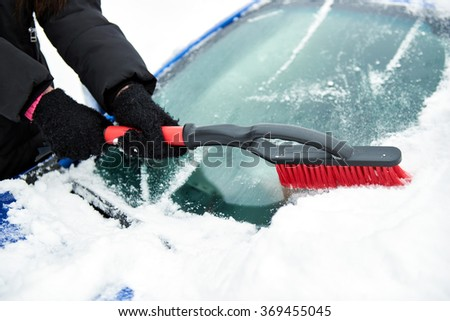 women hand in black glove removes snow from car windshield in winter day