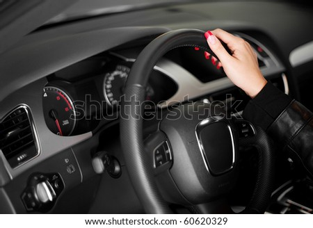 Women hand on the steering wheel of modern car - stock photo