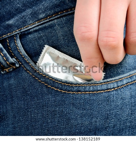 women hand reaching for condom in pocket - stock photo