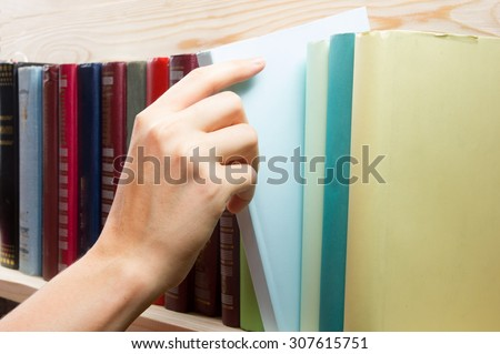 Women Hand selecting book from a bookshelf  in library. Back to school. - stock photo