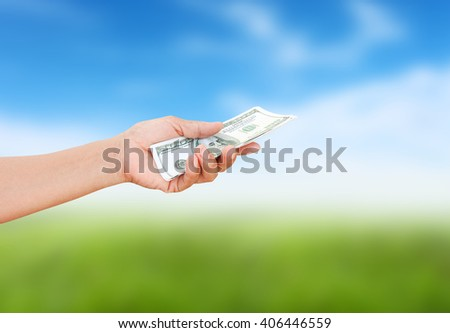 Women hand sent some money  on nature background.