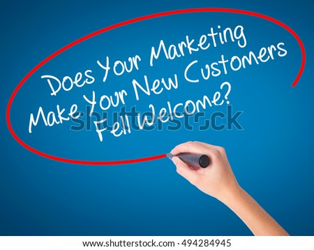 Women Hand writing Does Your Marketing Make Your New Customers Fell Welcome?  with black marker on visual screen. Isolated on blue. Business, technology, internet concept. Stock Photo