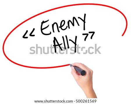 Women Hand writing Enemy - Ally with black marker on visual screen. Isolated on white. Business, technology, internet concept. Stock Photo
