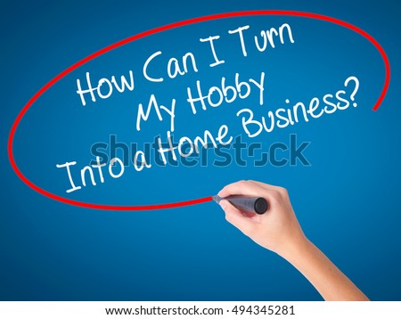 Women Hand writing How Can I Turn My Hobby Into a Home Business? with black marker on visual screen. Isolated on blue. Business, technology, internet concept. Stock Photo