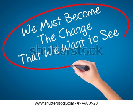 Women Hand writing We Must Become The Change That We Want to See with black marker on visual screen. Isolated on blue. Business, technology, internet concept. Stock Photo