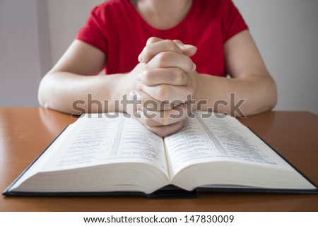 women hands folded in prayer over a holy bible - stock photo