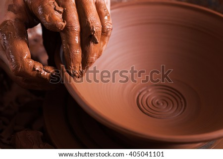 Women hands. Potter at work. Creating dishes. Potter's wheel. Dirty hands in the clay and the potter's wheel with the product. Creation. Working potter. - stock photo