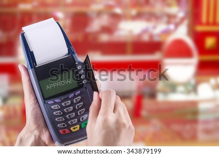Women Hands swiping Credit card on Credit card machine or Credit card Terminal on Gold shop background, with Clipping path - stock photo