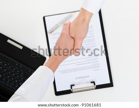 Women handshake of business partners, when signing contract.
