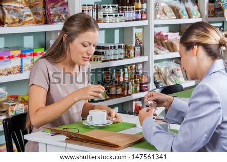 Women having coffee at table in grocery store - stock photo