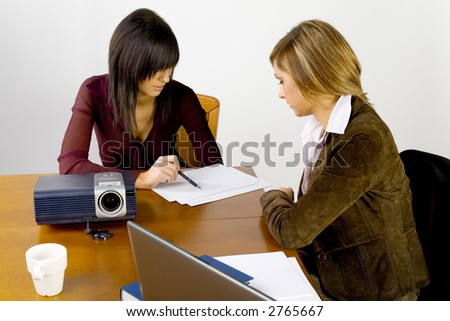 Women having conversation at conference's table. There's multimedia projector and laptop on it. - stock photo