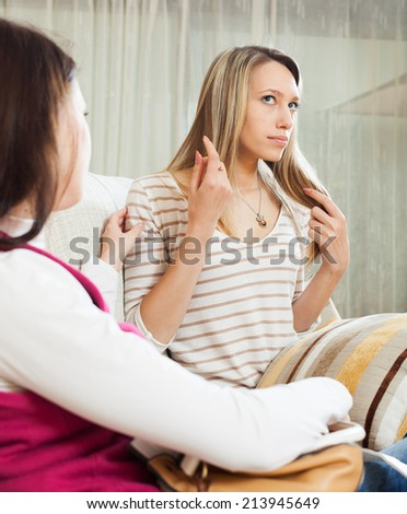 women having serious talking in home interior