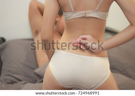 Women holding condoms in the background are men,About the prevention of sexually transmitted diseases.(selective focus,out of focus)