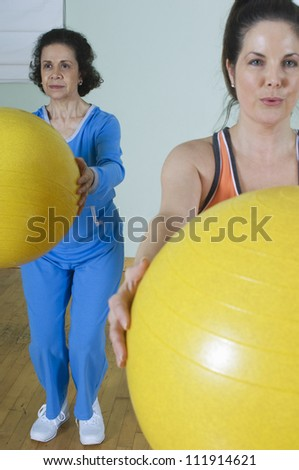 Women holding exercise balls in fitness class - stock photo