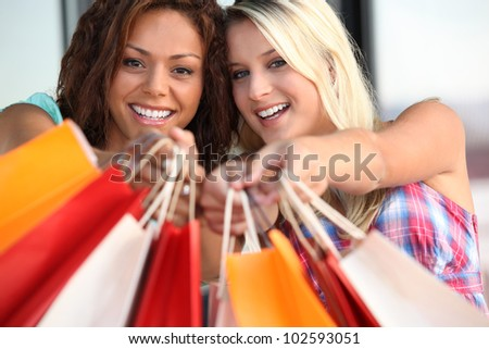 Women holding out their shopping bags - stock photo