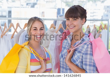 Women holding shopping bags and smiling to the camera
