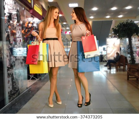 Women holding shopping bags are  doing purchase at  shop center. - stock photo