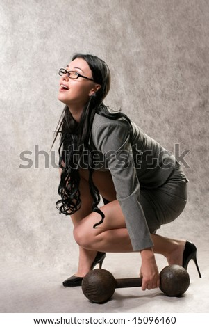 Women in a gray suit and an old dumbbell - stock photo