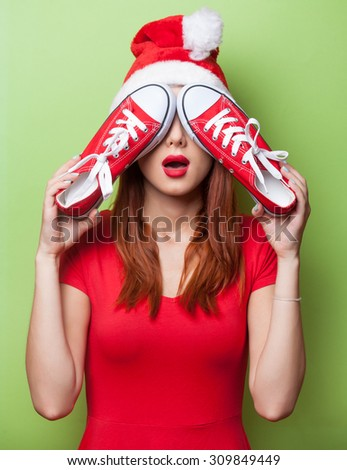 women in christmas hat with red gumshoes on green background. - stock photo