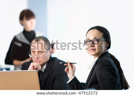 Women in glasses with pen and men - stock photo