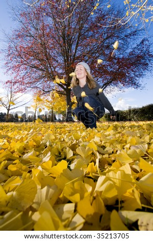 women In park surrounded by autumn leaves, New Zealand - stock photo