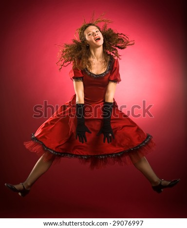 Women in red dress jumping on red background - stock photo