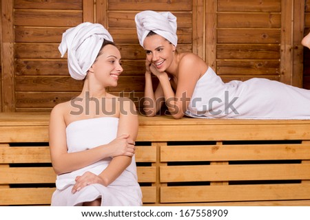 Women in sauna. Two attractive women wrapped in towel relaxing in sauna - stock photo