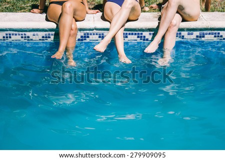 Women in swimsuit sitting on the edge of a pool