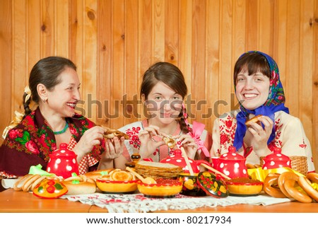 Women in traditional  clothes eating pancake with caviare during  Pancake Week