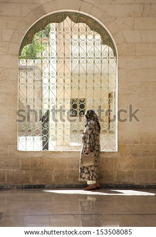 Women in traditional dress visiting famous Mosque  with ornate trellis arches in Sanliurfa, Turkey - stock photo