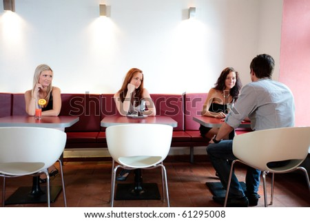 Women is sitting with a men with the other women looking in jealousy - stock photo