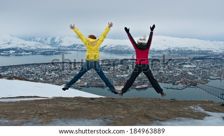 Women jump on the hill in Tromso, Norway. - stock photo